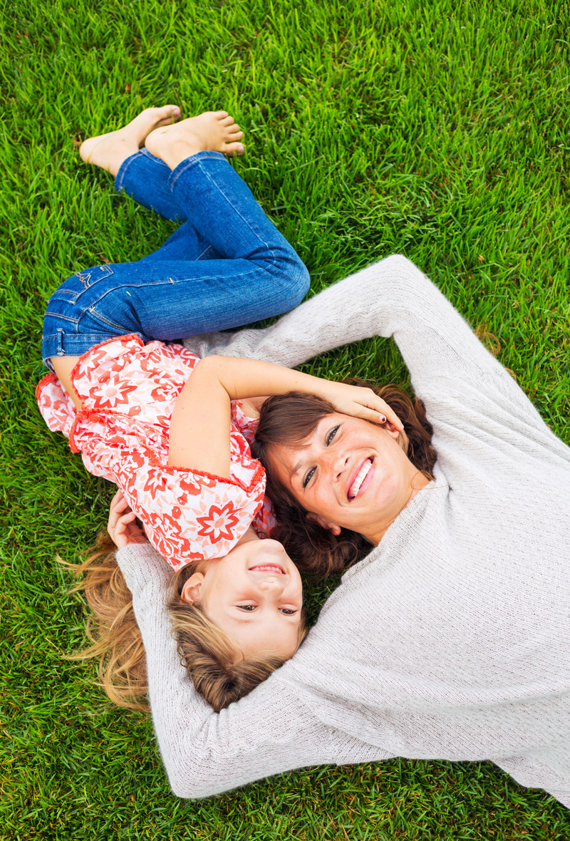 mother and daughter laying on the grass